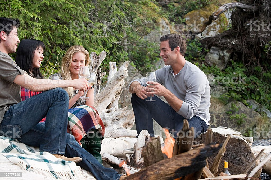 Four young people sitting around campfire stock photo
