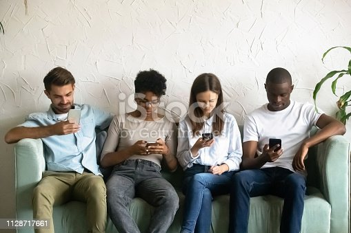 istock Four young people sitting on couch absorbed by smartphones 1128717661