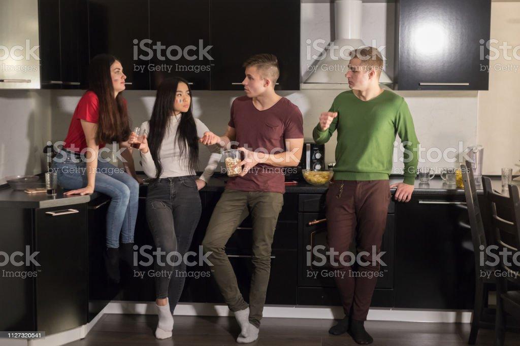 Four young people standing on kitchen and talking. Mid shot