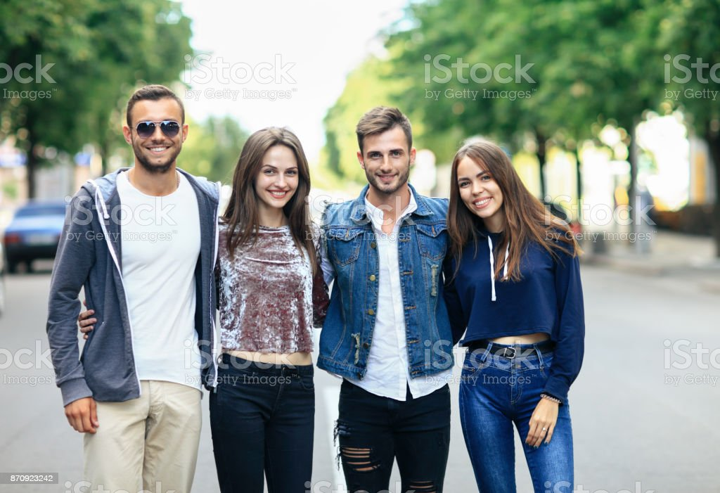Four young smiling friends walking on street on warm day stock photo