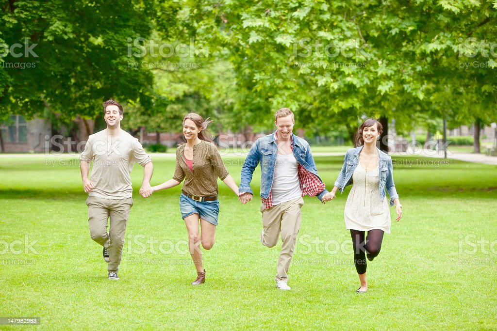 Four Young Smiling People Running in the Park royalty-free stock photo