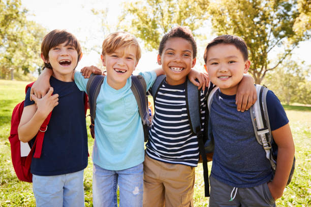 Four young smiling schoolboys hanging out on a school trip stock photo