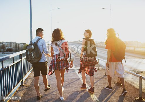 503545320istockphoto Four young student tourists walking over the bridge on a hot summer day. 1032716218