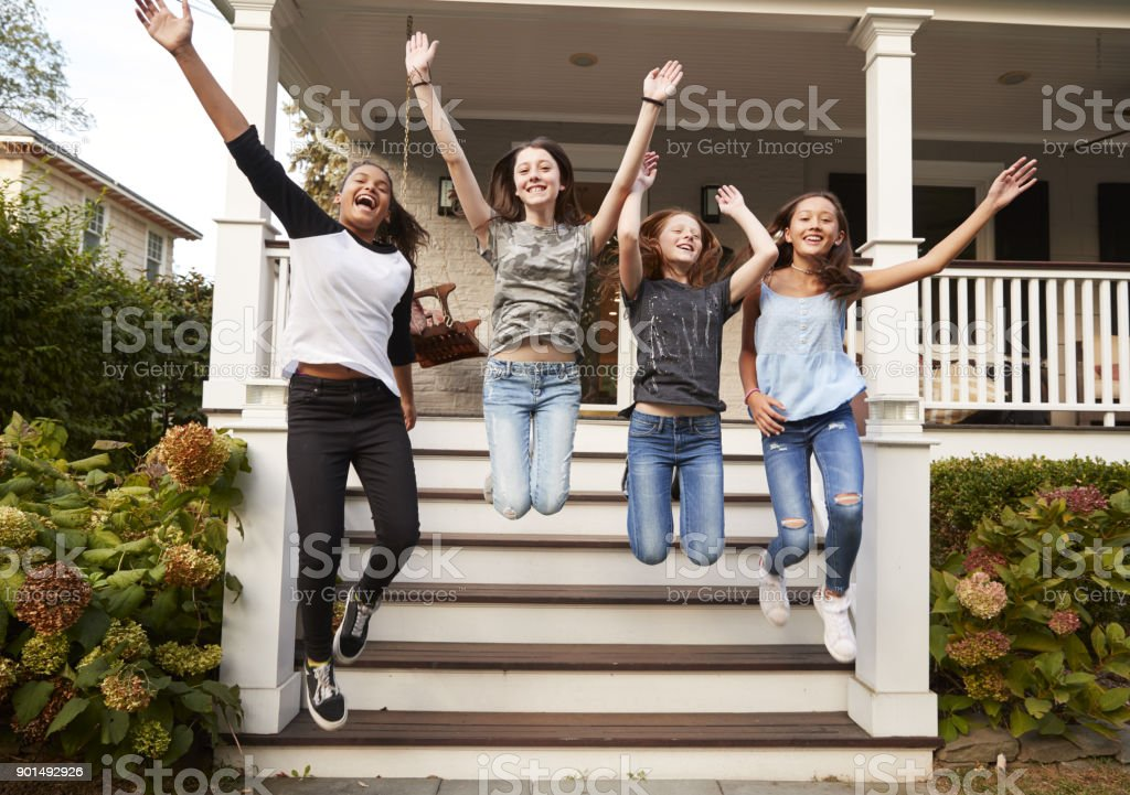 Four young teen girls jumping from front steps of a house stock photo