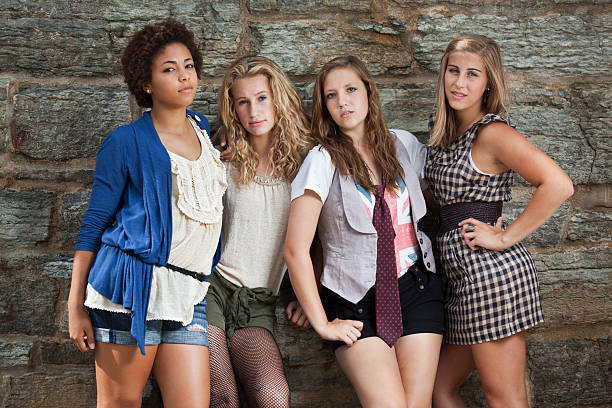 Four Young Teenage Girls, Best Friends Group by Stone Wall stock photo