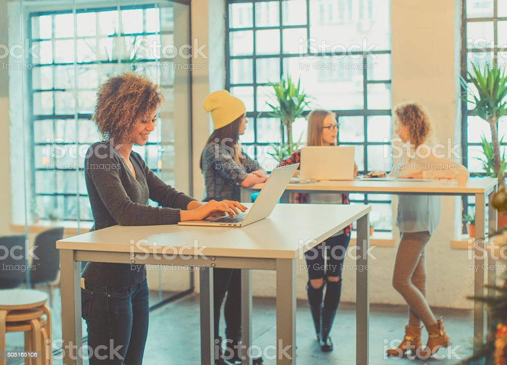 four young woman working at the office stock photo