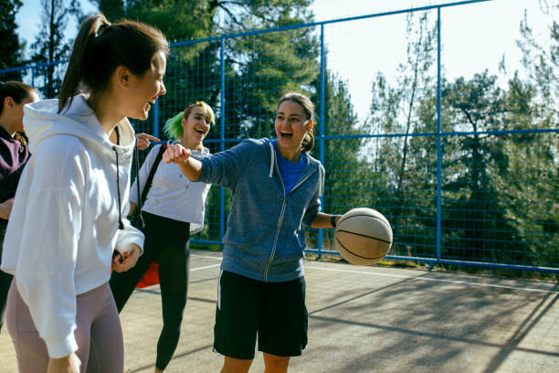 Four Young Women On The Court Ready To Play Basketball stock photo
