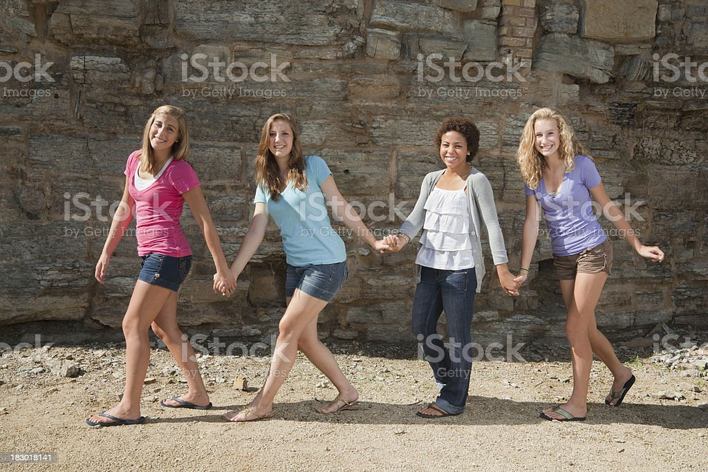 Four Young Women, Teenager Girl Friends Walking in a Row stock photo