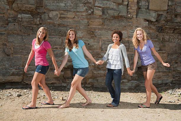 Four Young Women, Teenager Girl Friends Walking in a Row stock photo