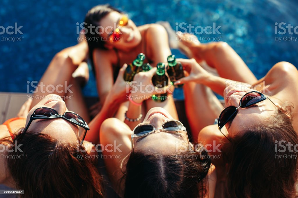 Four young women toast with a beer in the pool and smiling stock photo