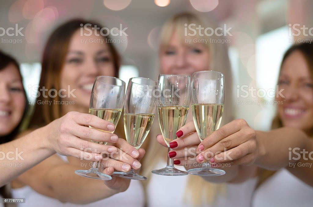 Four young women toasting with champagne stock photo
