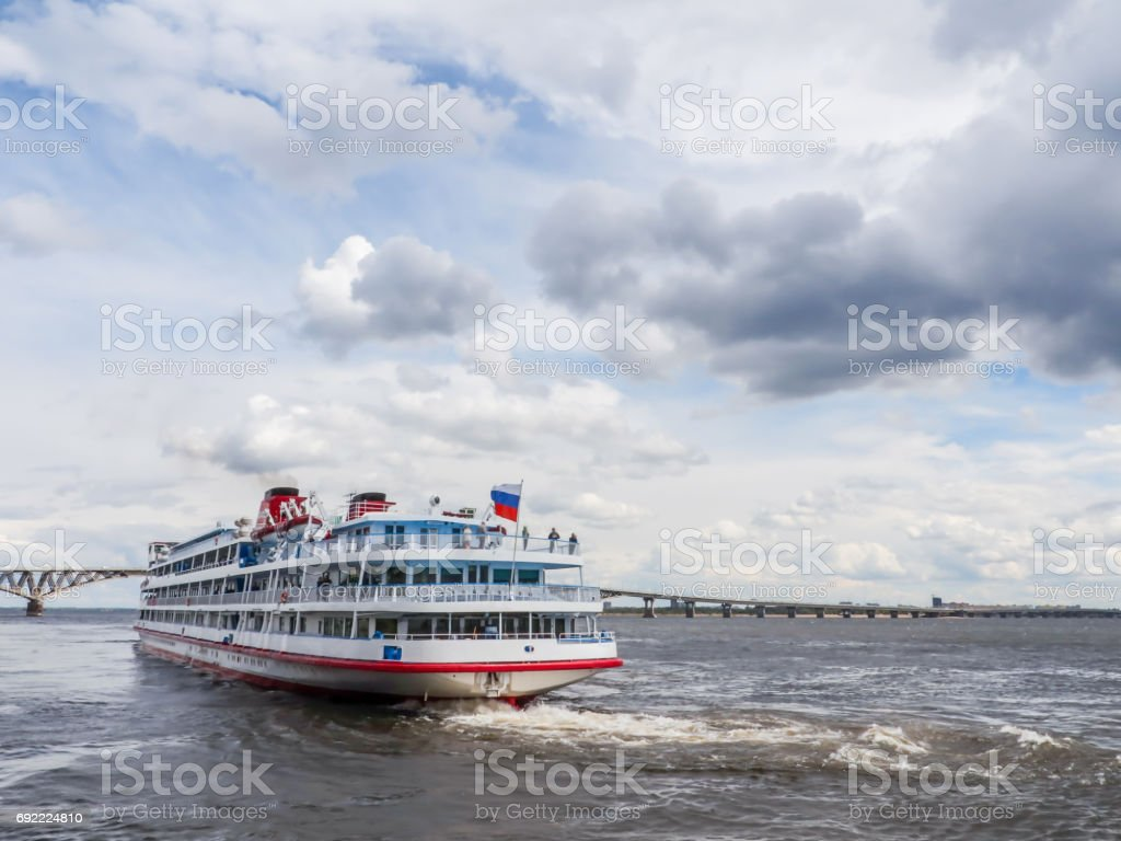 Four-deck passenger ship departs from the pier of the city of Saratov. On the horizon road bridge. The Volga River, Russia. White clouds on a blue sky stock photo