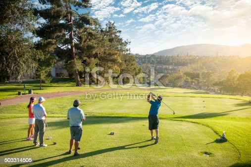 A man teeing off as his friends watch him hit on a beautiful day at the golf course.   http://blog.michaelsvoboda.com/GolfBanner.jpg