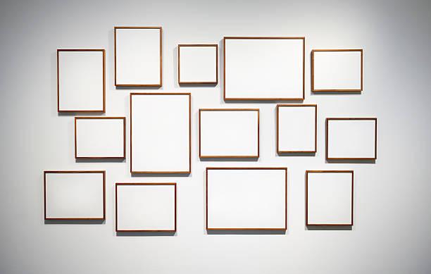Vierzehn leere hölzerne Bilderrahmen auf weiße Wand – Foto