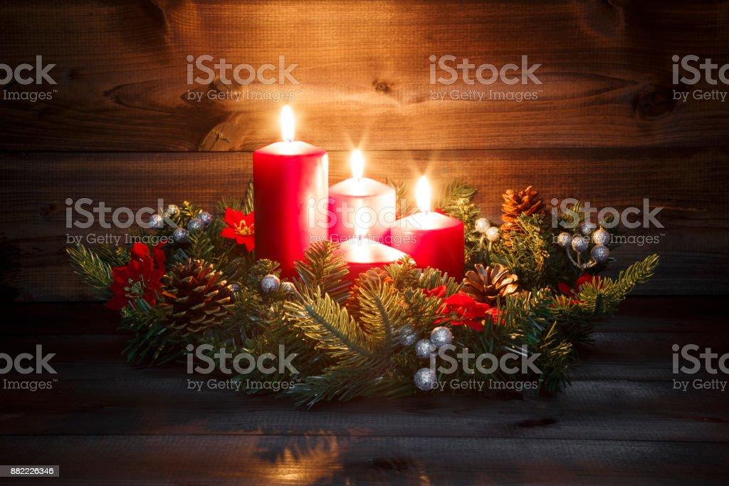 Cuarto Adviento - corona de Adviento con cuatro velas ardiente rojo sobre un fondo de madera con ambiente festivo - foto de stock