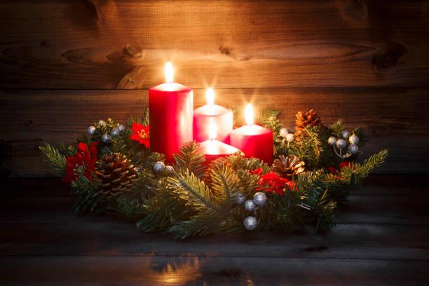fjärde advent - inredda advent krans med fyra röda brinnande ljus på en trä bakgrund med feststämning - advent bildbanksfoton och bilder