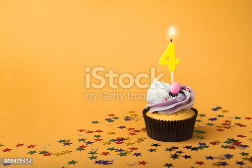 istock Fourth birthday cupcake with candle and sprinkles 935475454