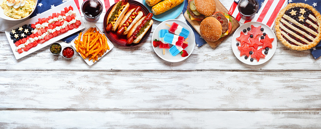 Fourth of July, patriotic, American themed food. Above view top border on a white wood banner background. Copy space.