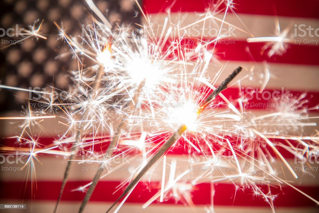 Fourth of July Background A stock photo of a USA stars and stripes flag with sparklers in the foreground. Perfect for designs and articles about the 4th of July and the USA. 2017 Stock Photo