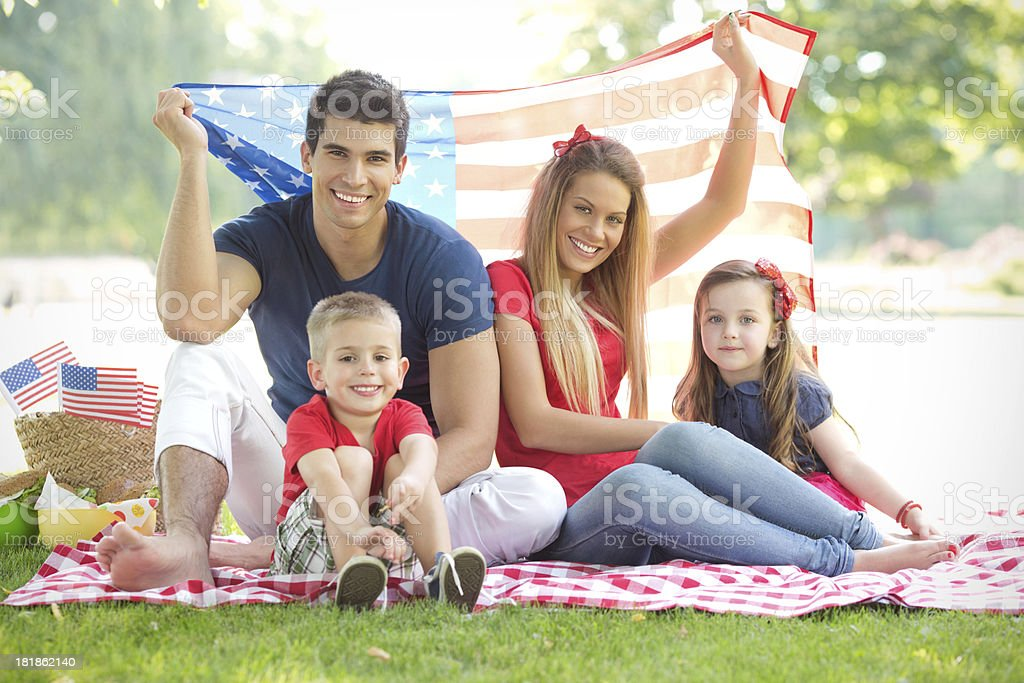 \'Parents with cute little children enjoying July 4th picnic, holding...