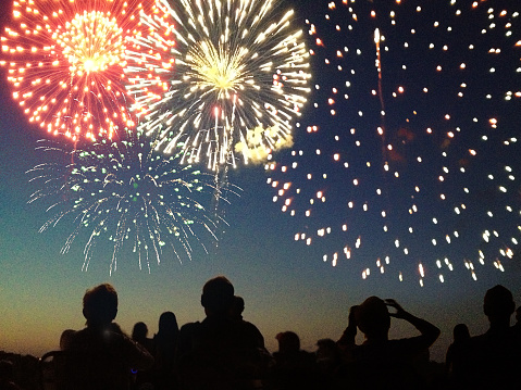 A Fourth of July fireworks display exploding in the sky over a group of people. The crowd, spectators in silhouette, celebrate the Independence Day national holiday together, looking up and watching bursts of color. The pyrotechnic performance may represent New Year's Eve, Chinese New Year, or other traditional festival celebration events.