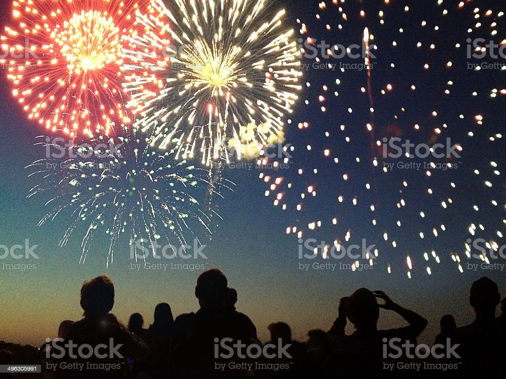 Fourth of July Fireworks Exploding Over Celebrating Spectators in Silhouette stock photo