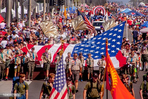 Boy Scouts march with a large US flag in a July 4th parade in Huntington Beach, CA.