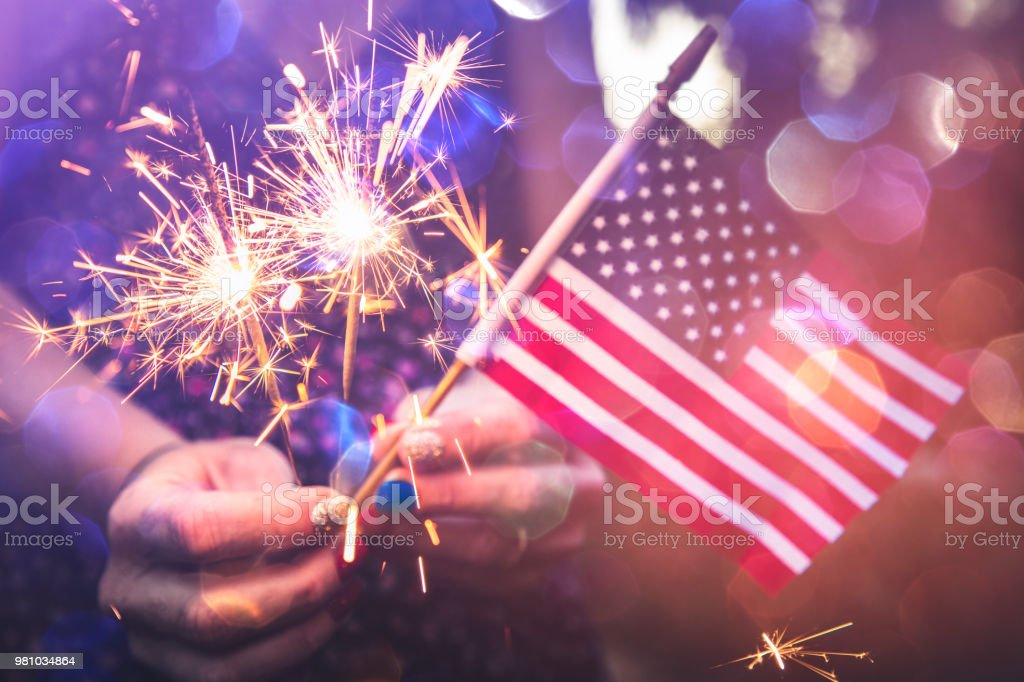 Fourth of July Fourth of July scene with sparklers and the American flag. Photographed in low light using the Canon EOS 1DX Mark II American Flag Stock Photo