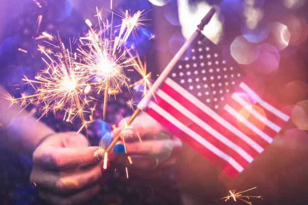 Fourth of July Fourth of July scene with sparklers and the American flag. Photographed in low light using the Canon EOS 1DX Mark II independence day photos stock pictures, royalty-free photos & images