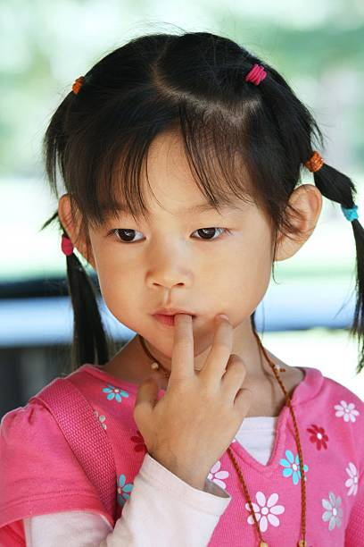 four-year-old girl in thought stock photo