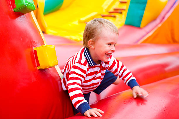 Four-year-old kid playing on a trampoline outdoor stock photo