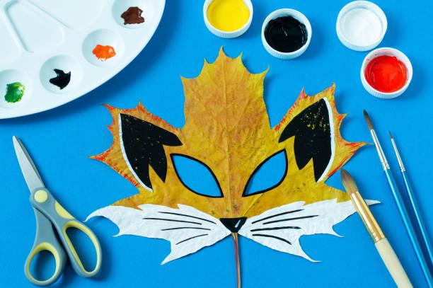 Fox mask painted on maple leaf stock photo