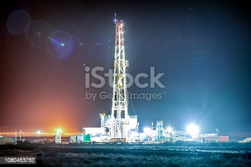 Night shot of a brightly lit fracking drill rig