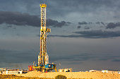 Beautiful clouds hanging over a modern fracking drilling rig in the western US