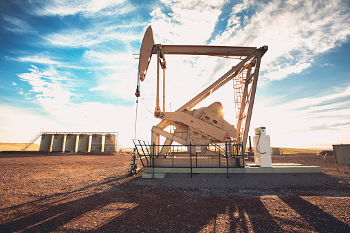 Industrial Fracking Oil Well pumping natural resourcesFracking Oil Well is conducting a fracking procedure to release trapped crude oil and natural gas to be refined and used as energy
