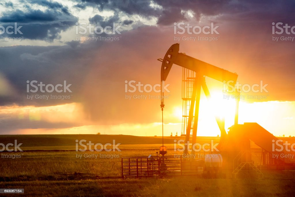 Fracking Pump Jack Under a Dramatic Sky with Setting Sun stock photo