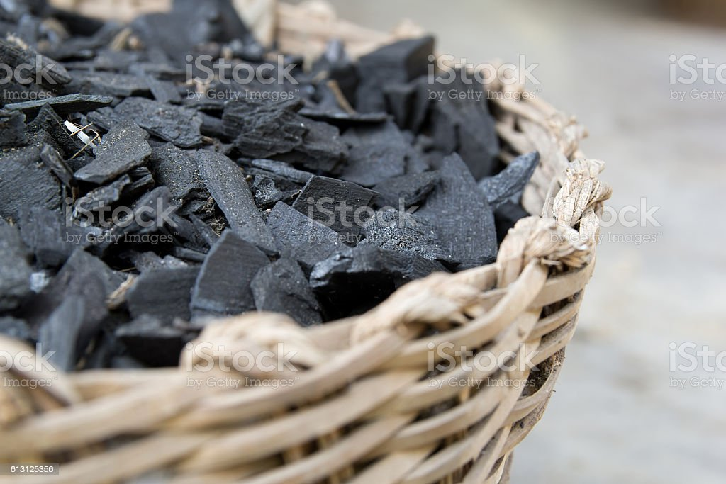 fraction of dust charcoal in the woven basket stock photo