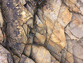 fractured rock strata as a background, cracked rock, stone texture, many cracks in the stone, fractured rock