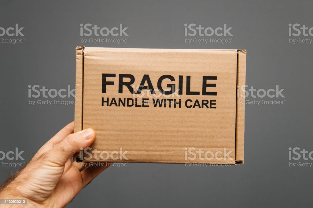 Fragile handle with care warning text on cardboard with text sign in...