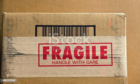 Fragile sign on shipping box with barcode being read by a thin red laser.