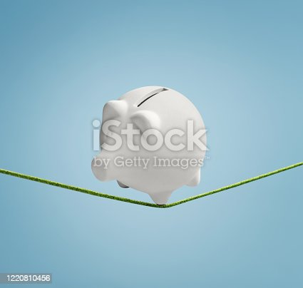 Piggy bank balancing precariously on a thin line ready to fall down