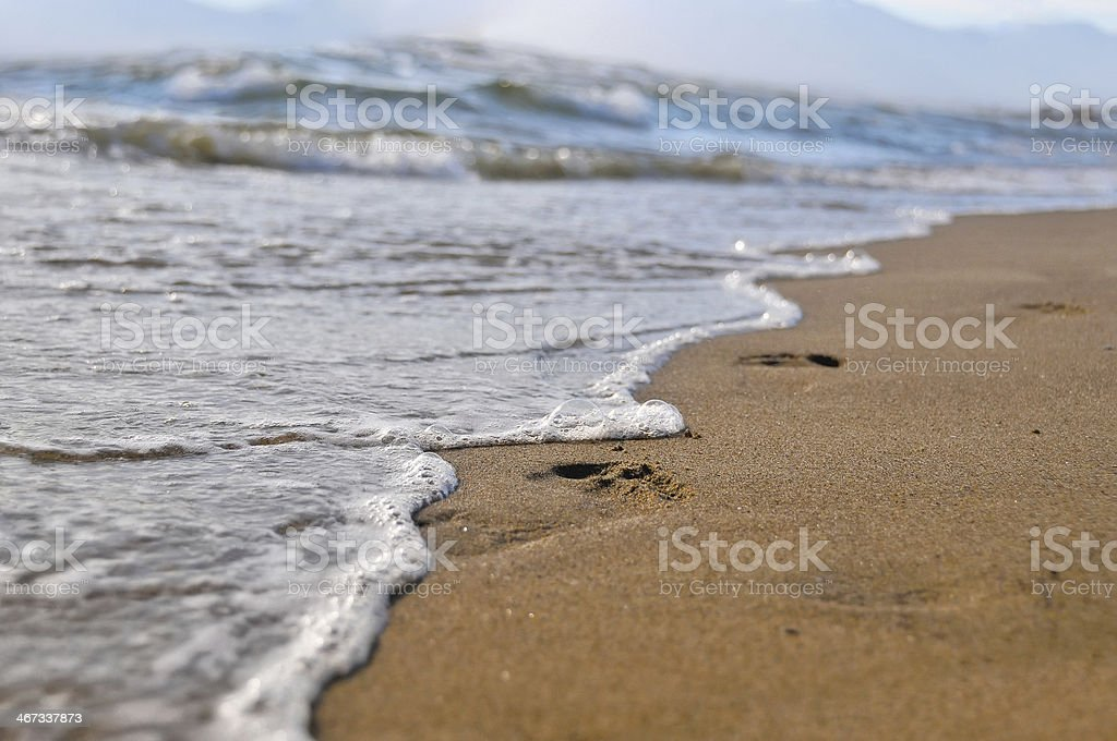 The wave washes footprints in the sand. Fragility.