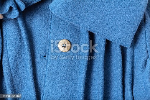istock Fragment of a button and collar with folds of a fashionable blue woolen coat 1220168162