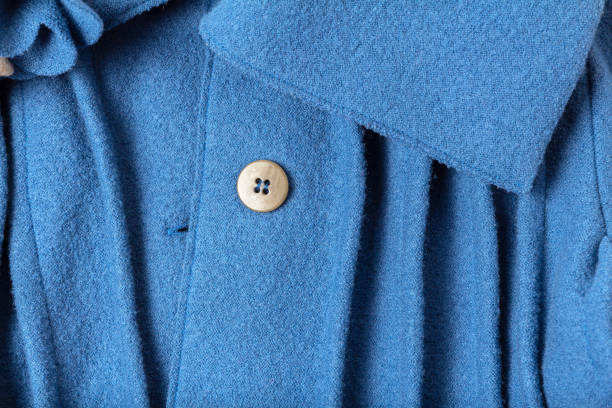 Fragment of a button and collar with folds of a fashionable blue woolen coat stock photo