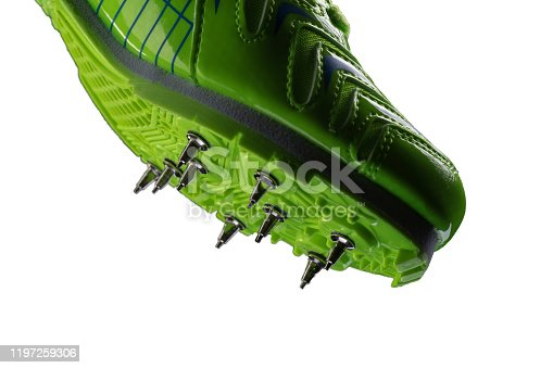 istock Fragment of a green glossy sneaker with spikes on a white background. Sport shoes. 1197259306