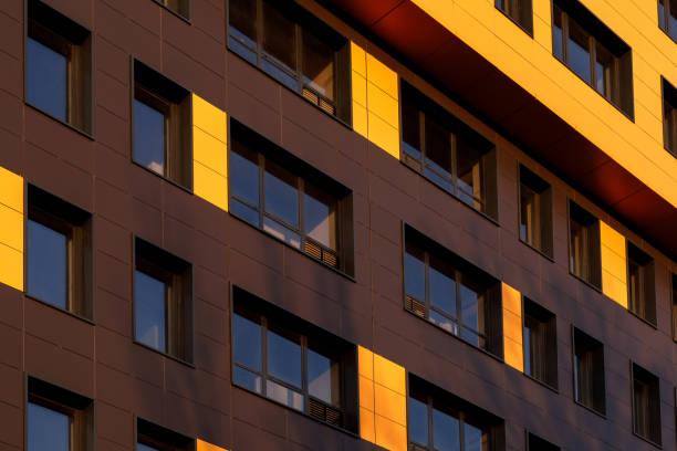 Fragment eines neuen Elitären Wohngebäudes oder Gewerbekomplexes. Teil der städtischen Immobilien. Gelbbraune, moderne belüftete Fassade mit Fenstern. – Foto