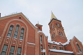 Fragment of a red brick church with windows and gilded roof.