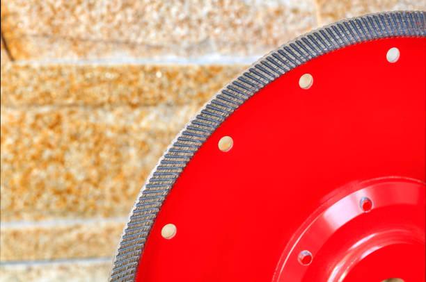 fragment einer roten diamantklinge zum schneiden von granit und stein vor dem hintergrund einer wand aus goldenem sandstein. - europäisch geschliffene diamanten stock-fotos und bilder