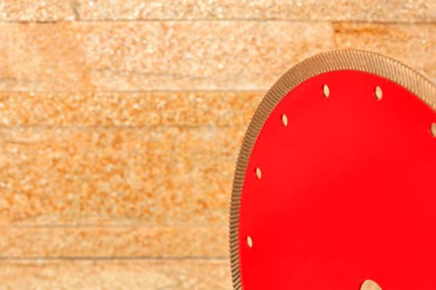 ein fragment einer roten diamantklinge zum schneiden von granit wird an die wand aus goldenem sandstein gedreht. - europäisch geschliffene diamanten stock-fotos und bilder