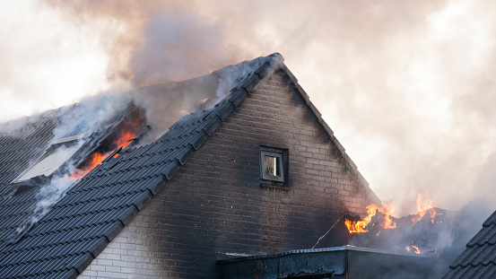 Semi detached white brick wall home with black tiles on the roof is on fire, flames are coming out of the roof while the fire brigade (off camera) is beginning to get the situation under control using a water tender -  the semi-detached house is situated in a suburb, its dormer has turnes black from soot